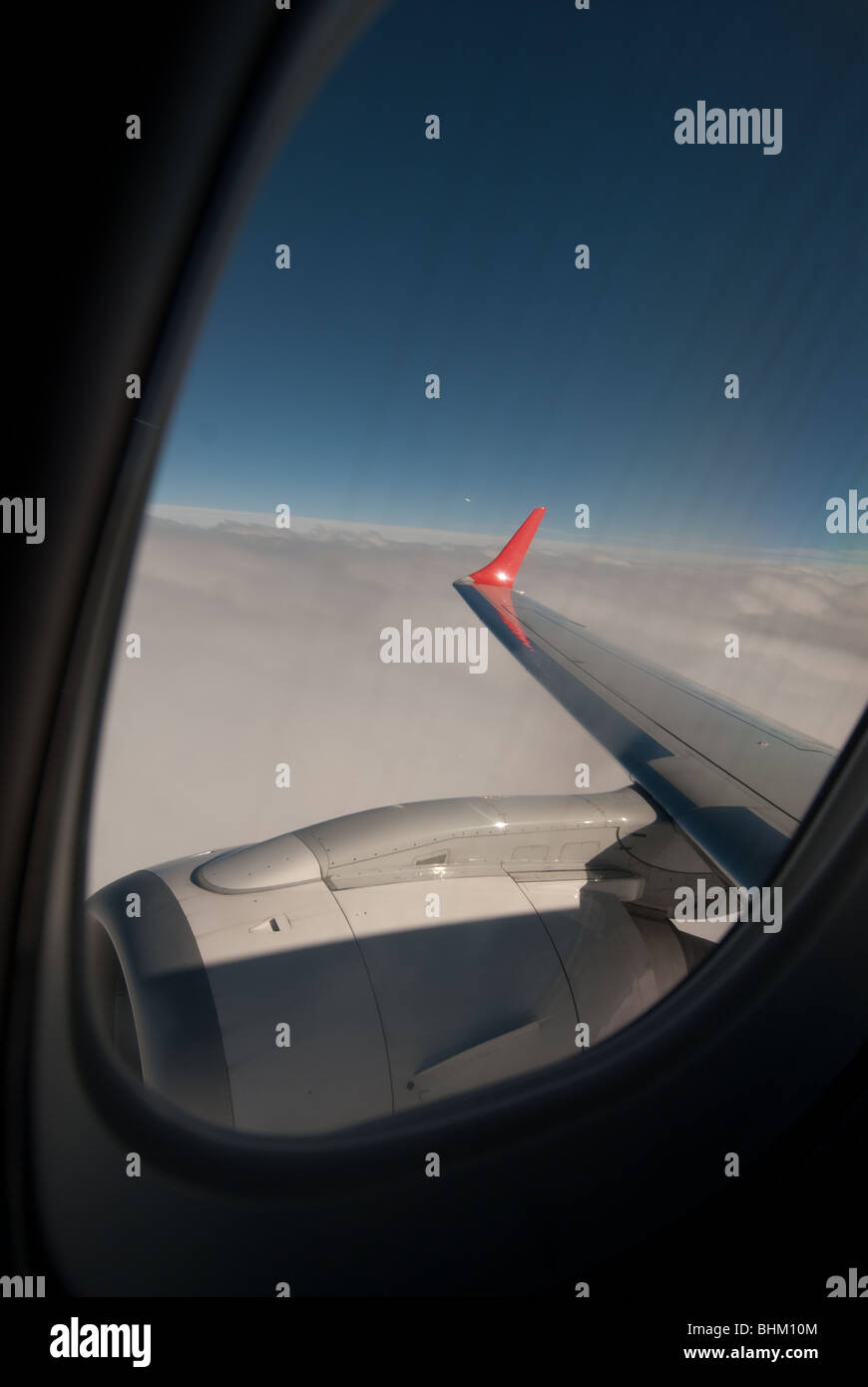 View over airoplane wing across the sky on a domestic passenger flight. - Stock Image