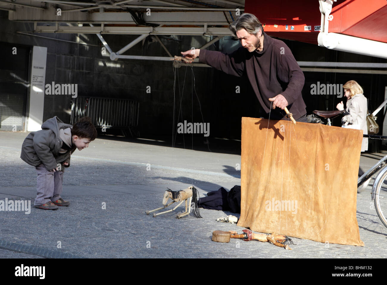 Puppeteer with marionette and small boy, Paris, France - Stock Image