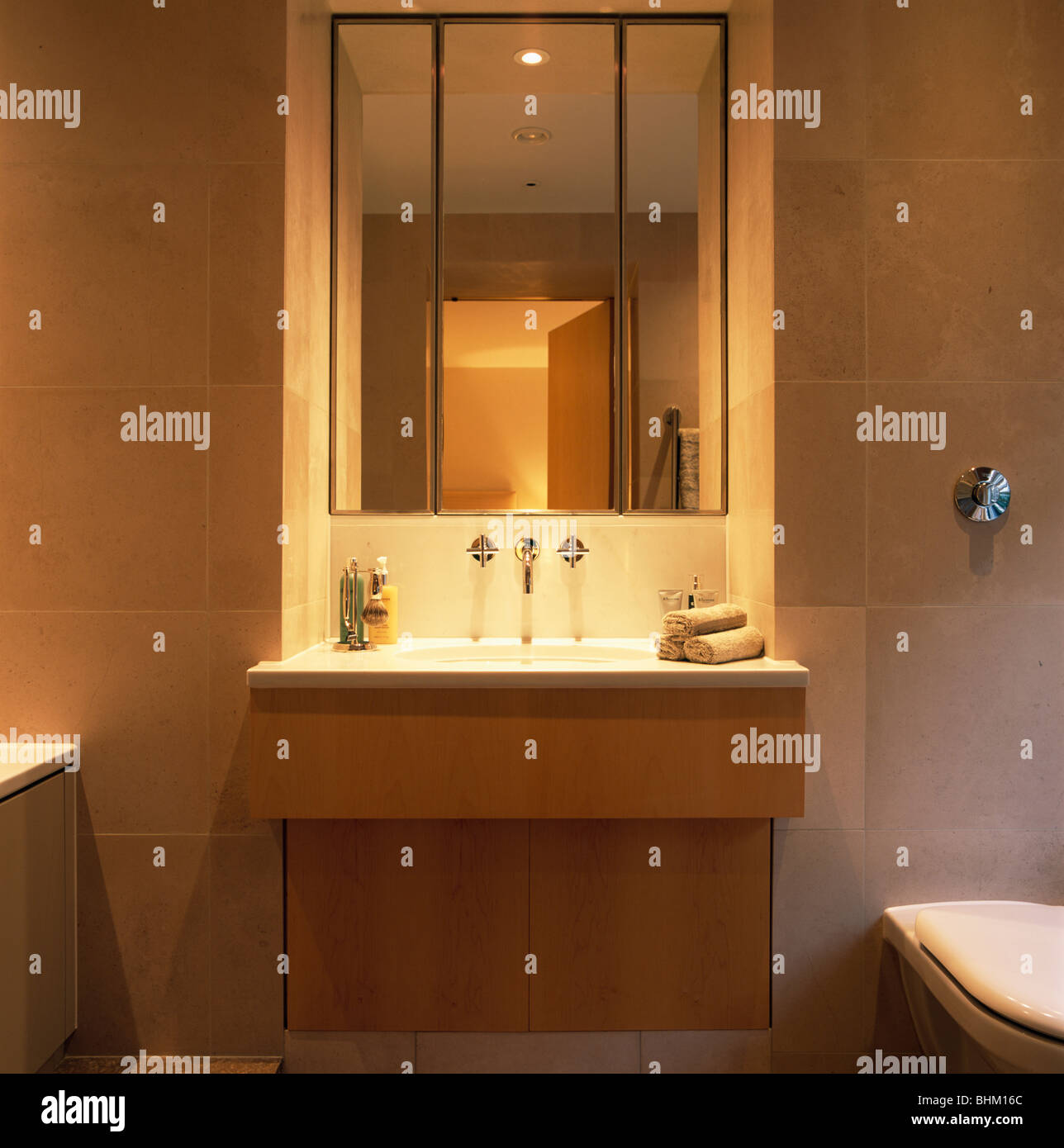Lighting and mirror above basin in vanity unit in modern bathroom ...