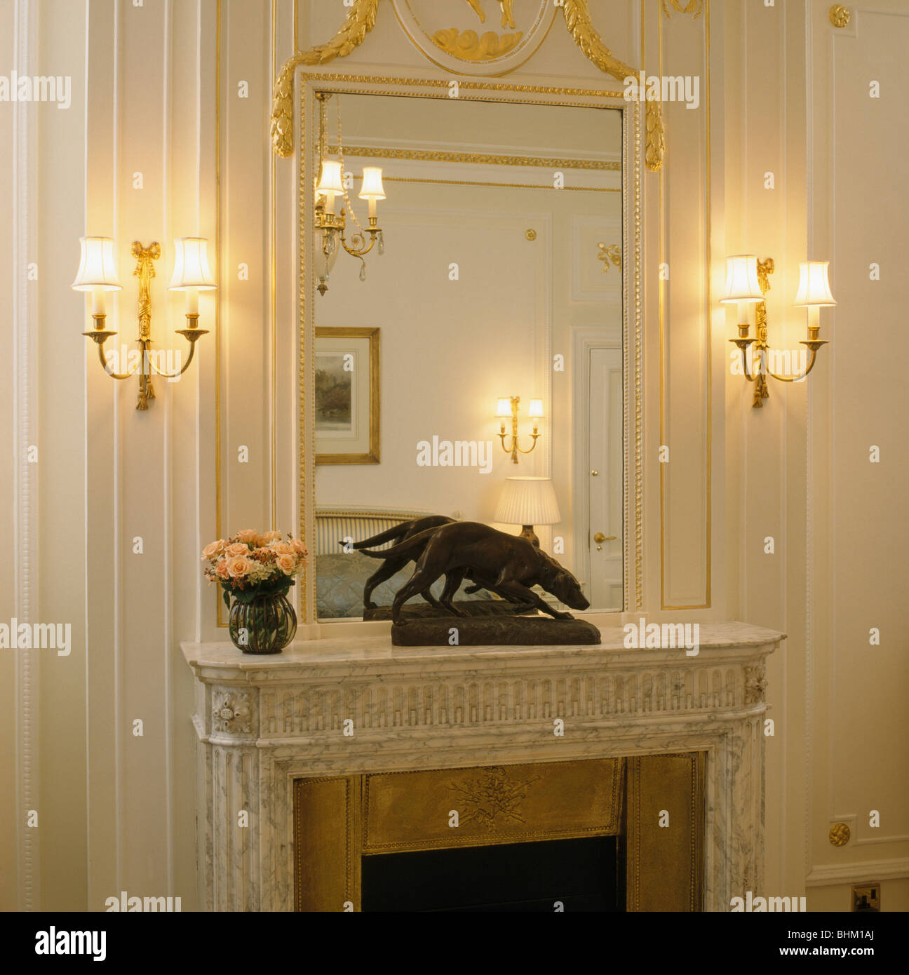 Lighted wall-lights on either side of over-mantel mirror above ...
