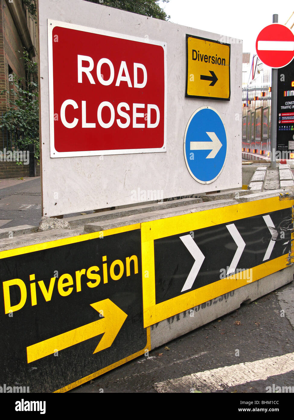 Road signs including road closed, diversion, arrows, no entry and chevrons blocking a trough road - Stock Image