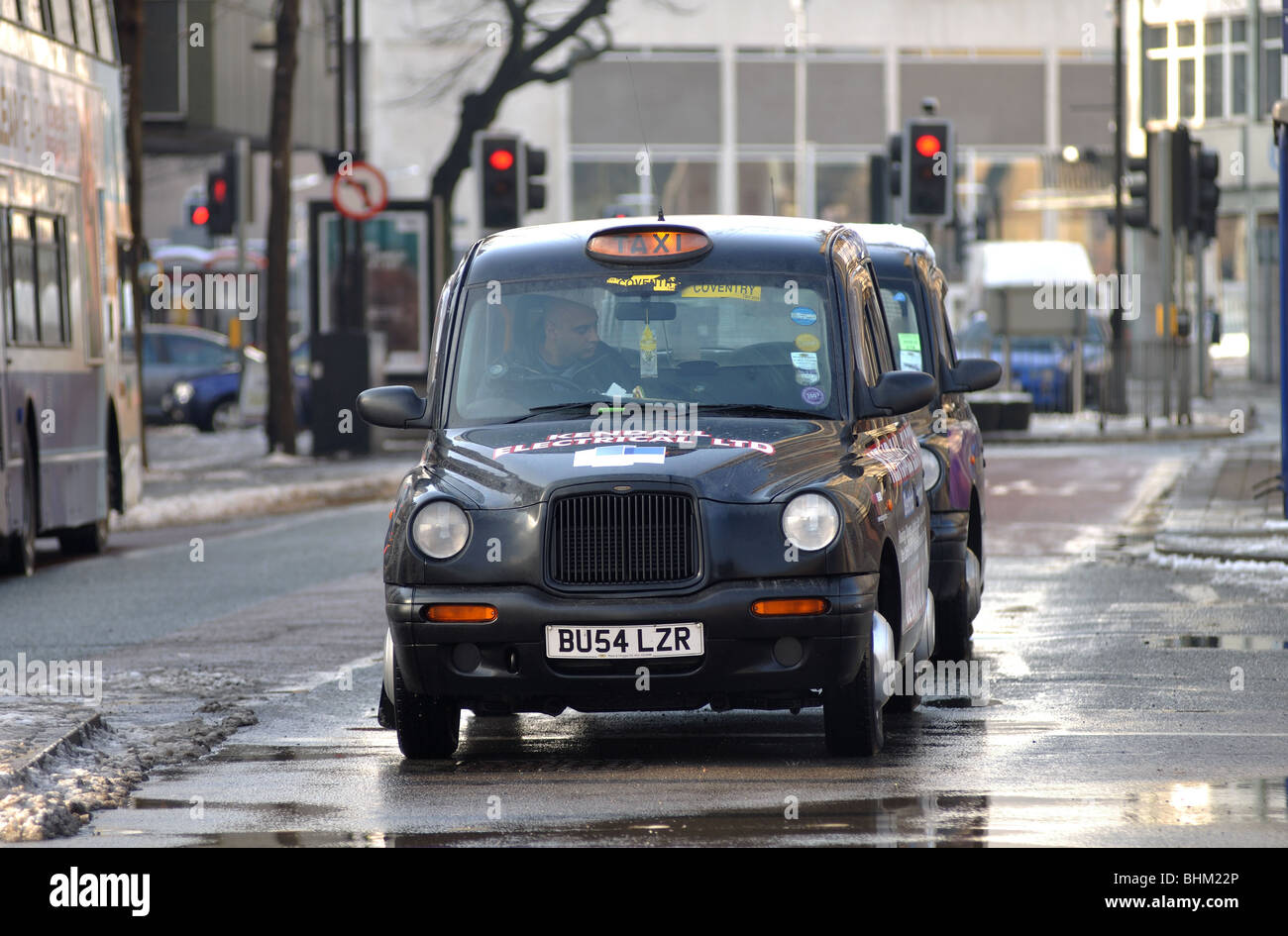 Taxi in Coventry city centre in winter, England, UK - Stock Image