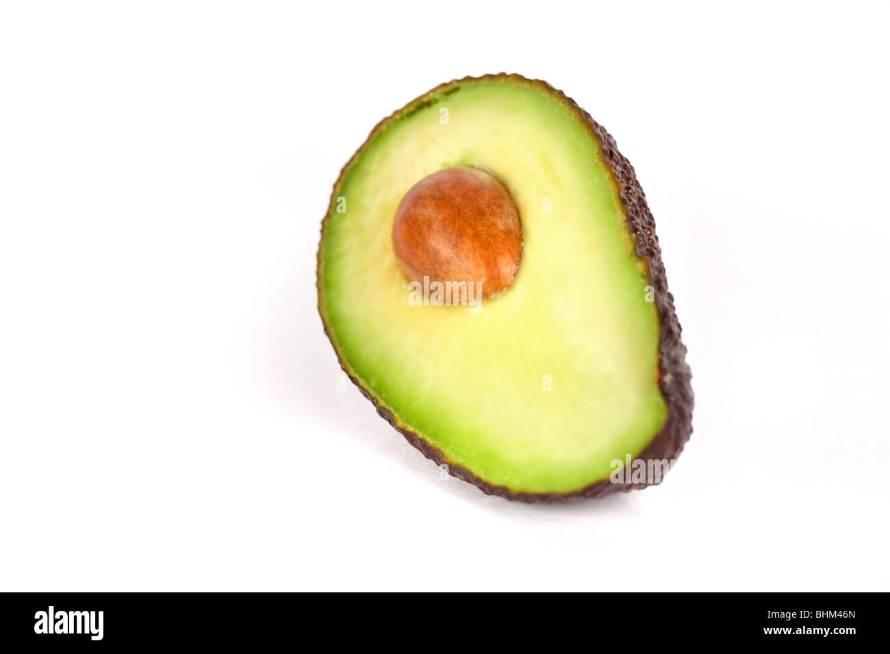 One avocado half with the stone/core on plain white background - Stock Image