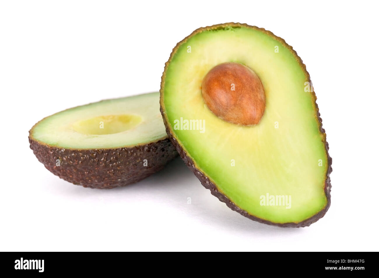 Two avocado halves on plain white background, one half with the stone/core. - Stock Image
