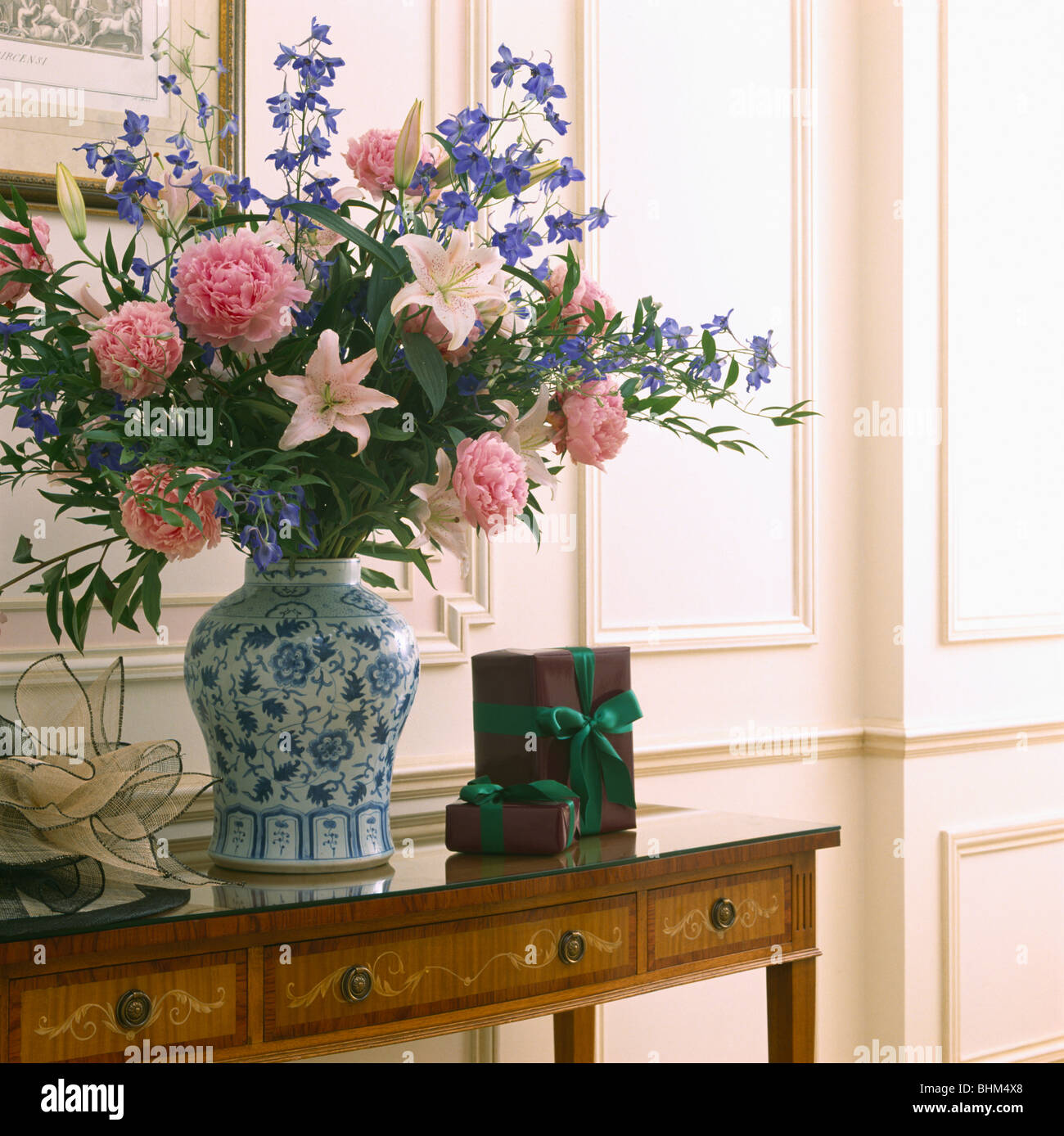 Close up of informal flower arrangement of pink and blue flowers in close up of informal flower arrangement of pink and blue flowers in blue white vase on antique console table mightylinksfo