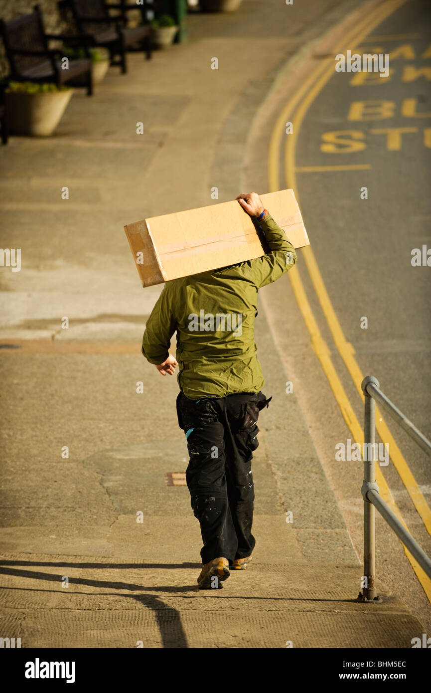 A man carrying a large package on his shoulders, back walking down the street, UK - Stock Image