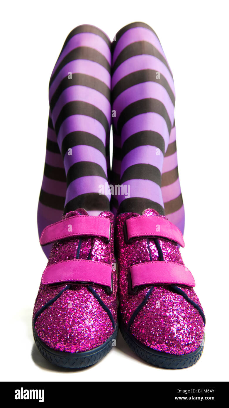 Pink sparkle shoes with woman legs in purple striped tights or pantyhose - Stock Image