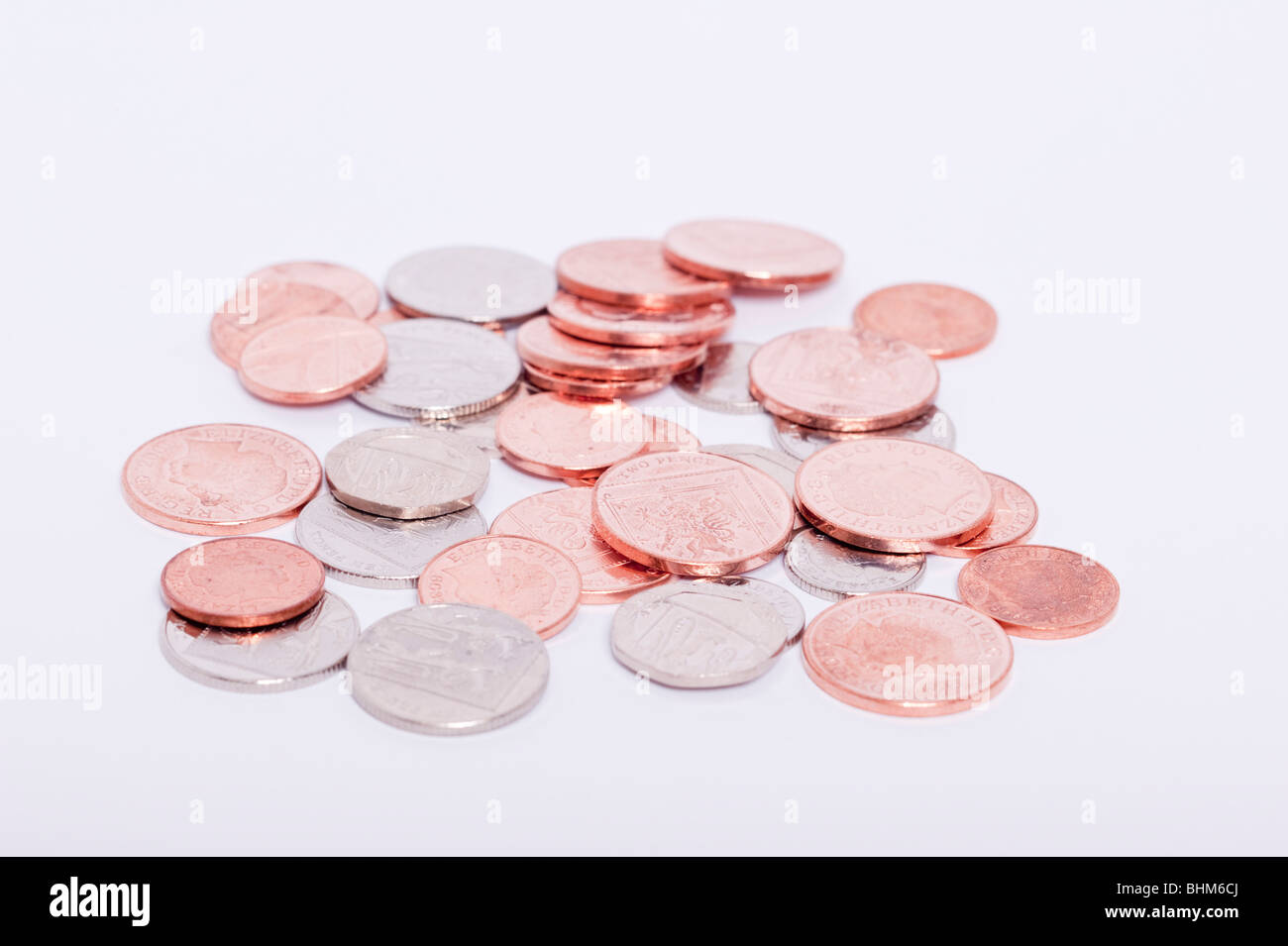A selection of Uk currency coins ( coppers & silver ) on a white background - Stock Image