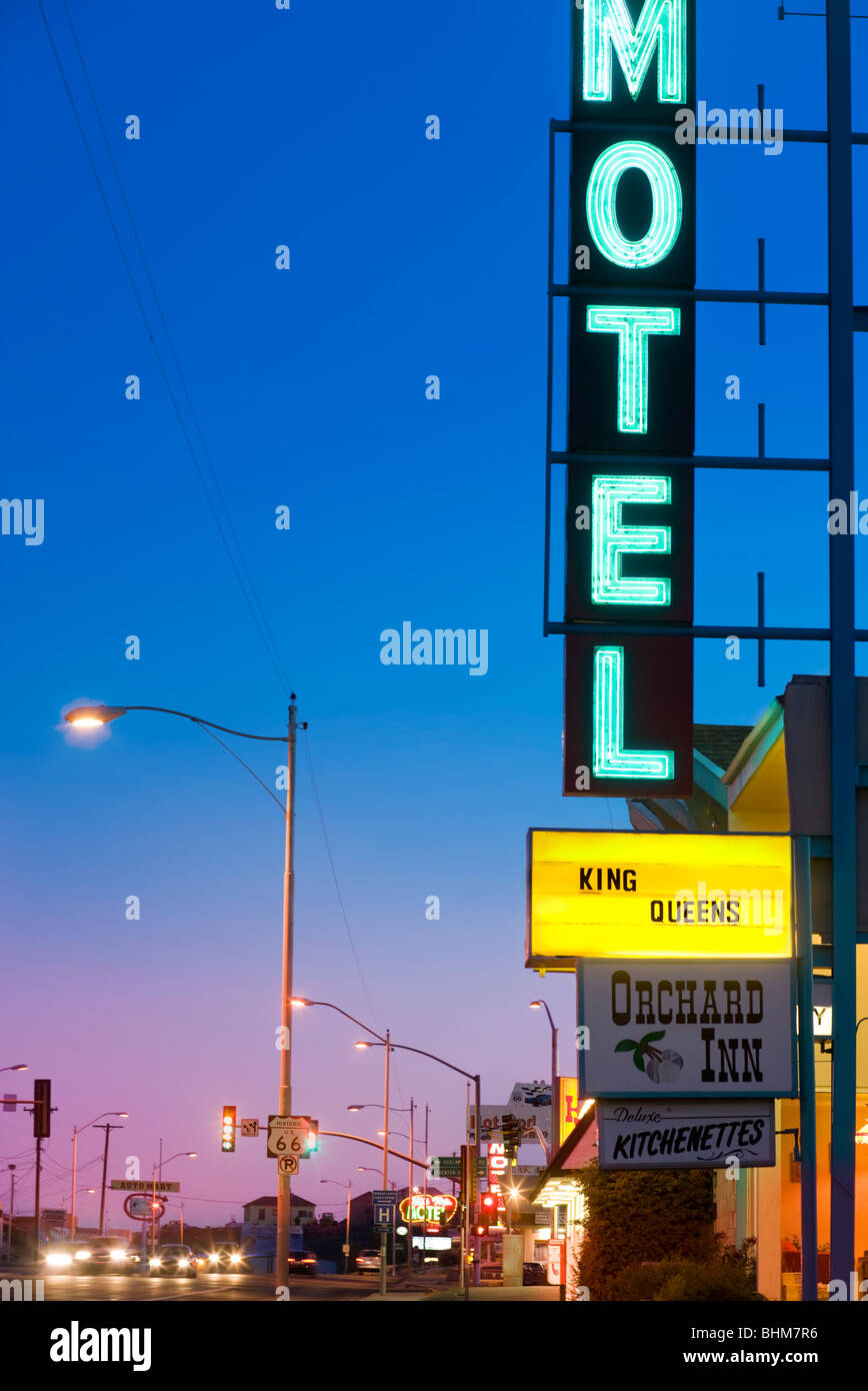 Neon Motel sign at the Orchard Inn in Kingman Arizona along historic US Route 66. Route 66 shield in front. At dusk. - Stock Image
