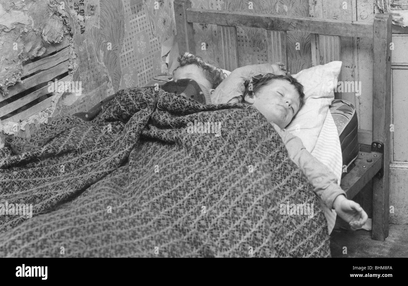 Children asleep in a slum dwelling in London's East End, 1965. - Stock Image