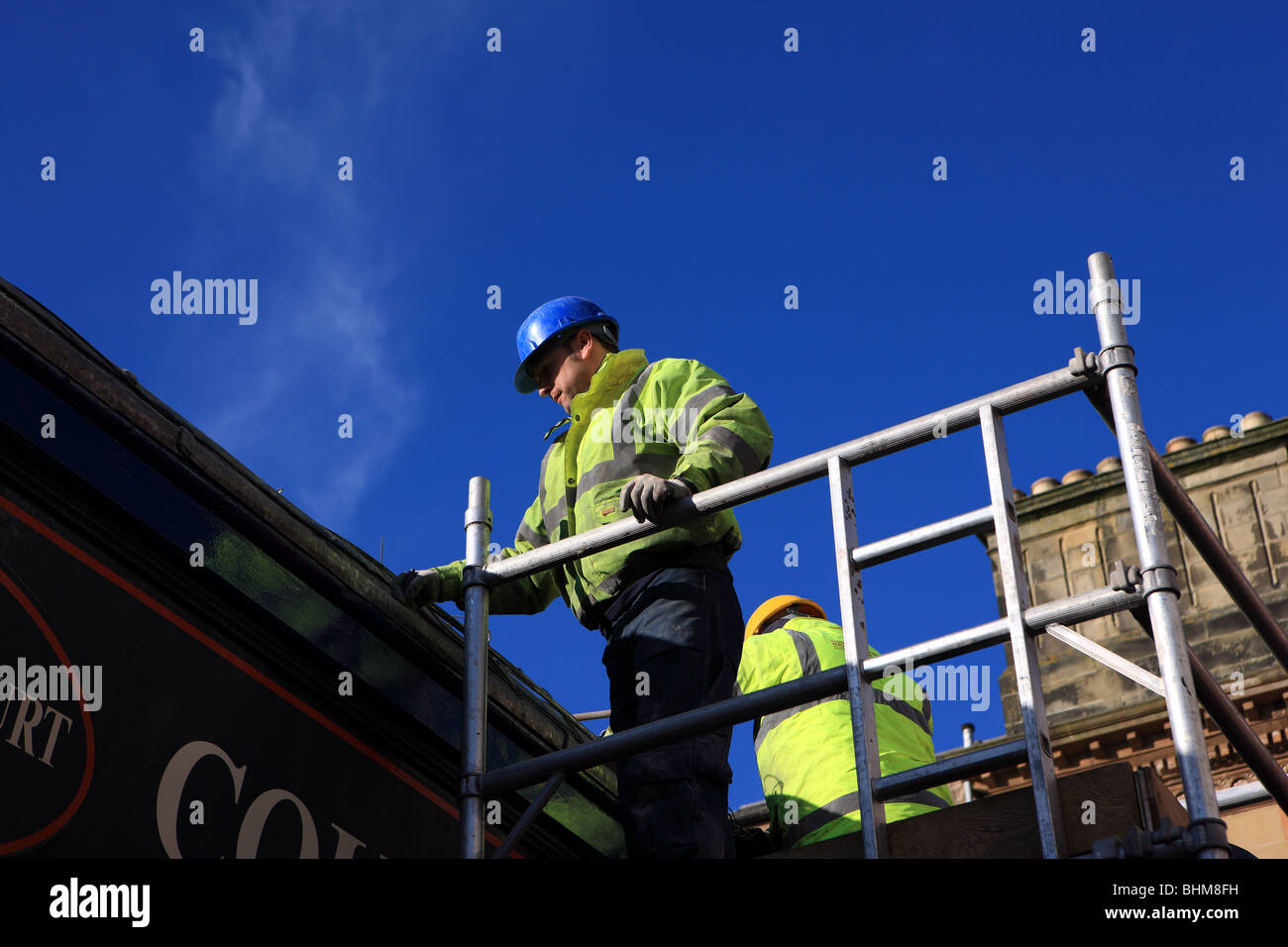 Workmen standing on scaffolding working on a shop roof - Stock Image
