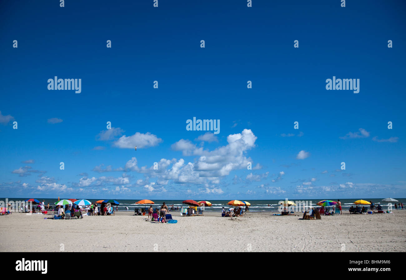 People on beach with deckchairs and sunshades Galveston Texas USA - Stock Image