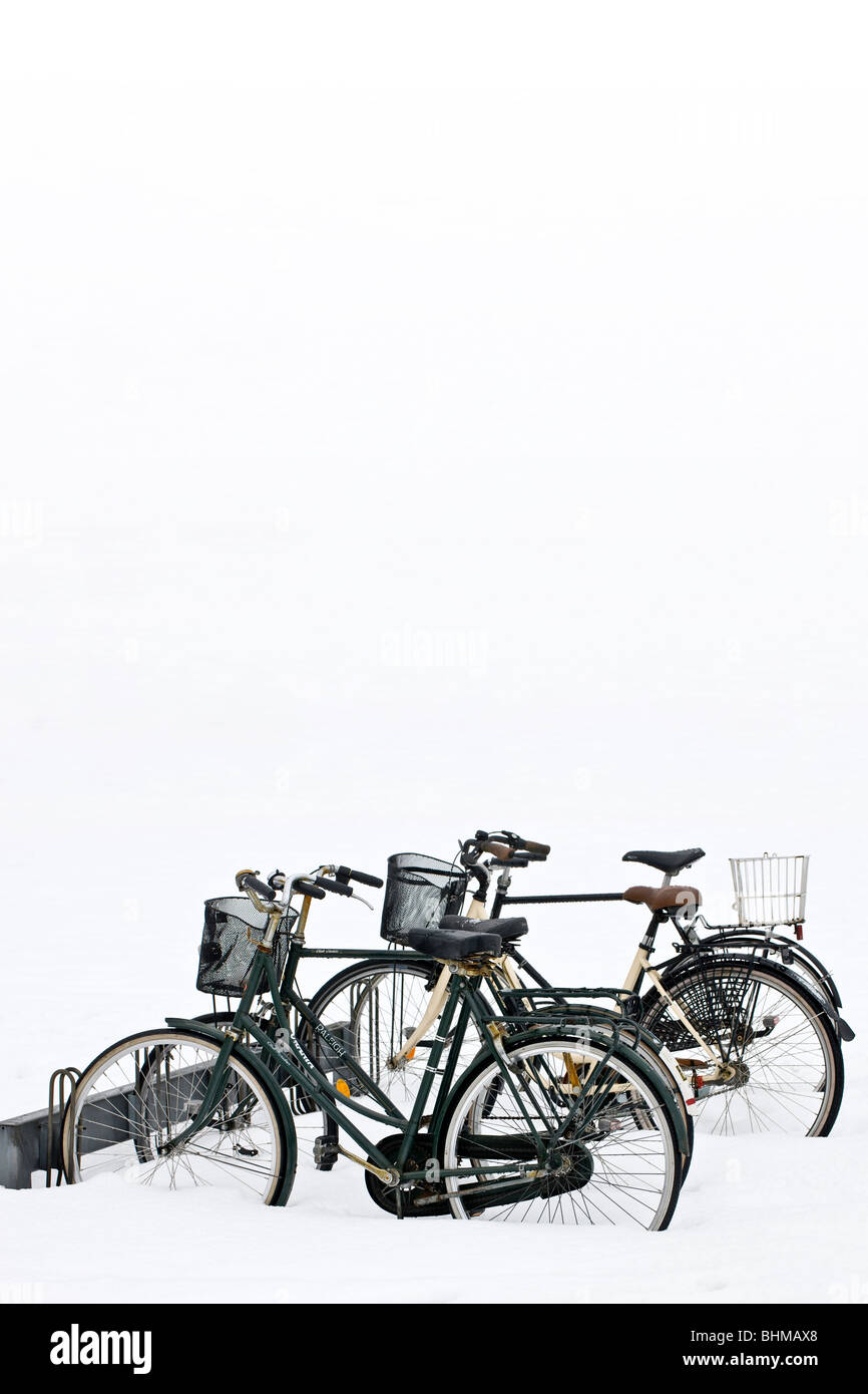 Four bicycles parked in the snow - Stock Image