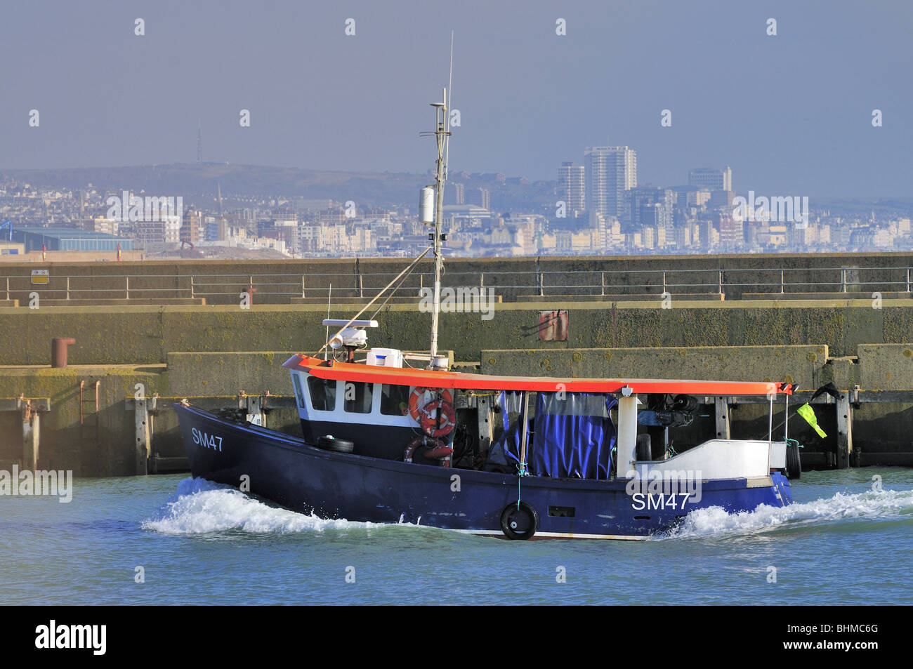 Small boat entering port ,harbour,Brighton ,Skyline Stock Photo