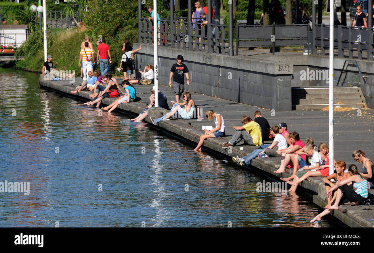 People barefoot  sitting on a pierce waterfront cooling their feet in the water of the Alster in the city of Hamburg, Stock Photo