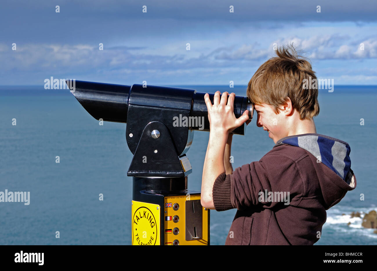 a young boy looking through a telescope at lands end in cornwall, uk - Stock Image