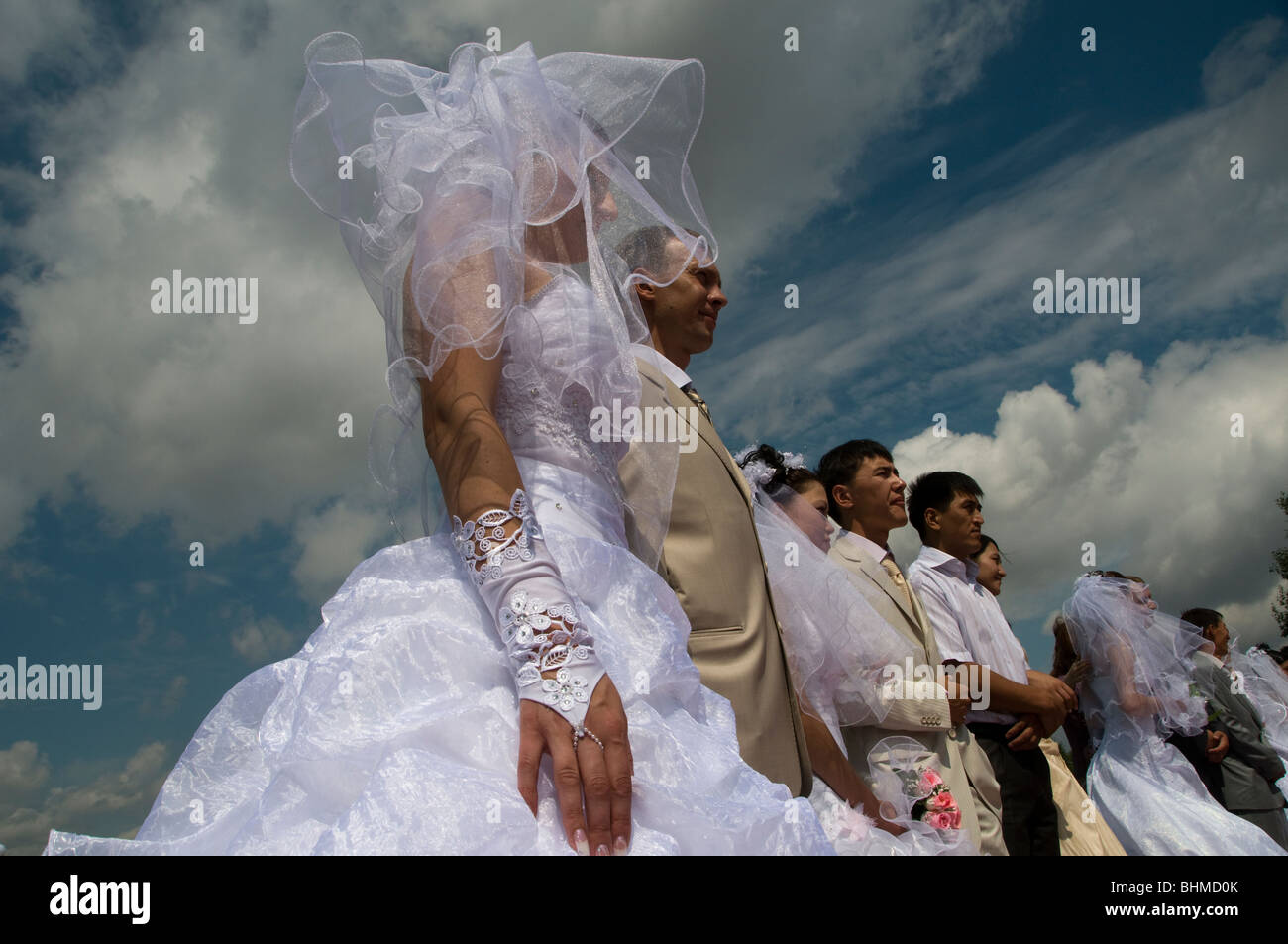 Kazakh brides and grooms in a simultaneously pre wedding photography session before mass wedding ceremony in Arai - Stock Image
