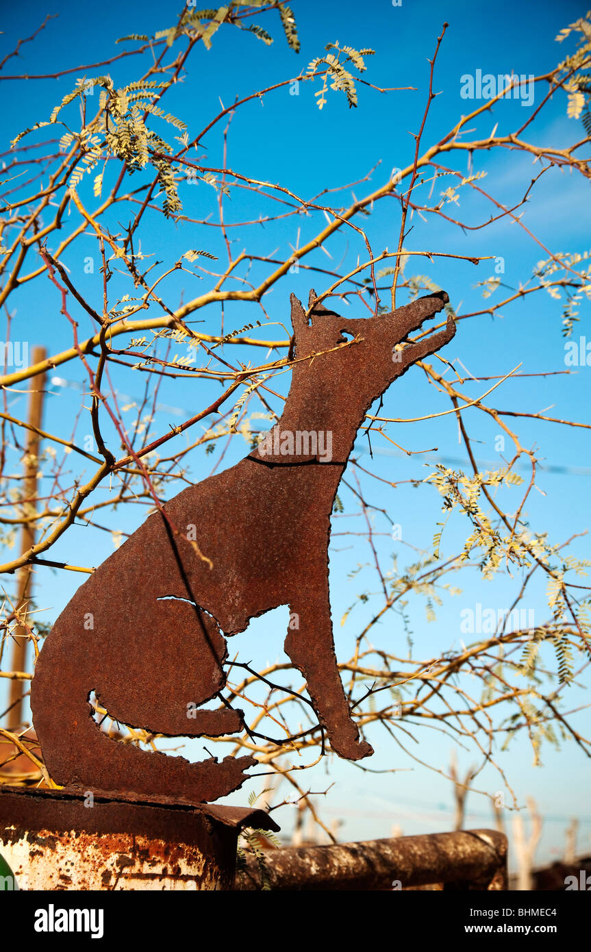 A metal coyote sign on a fence on the Gila Indian Reservation Stock Photo