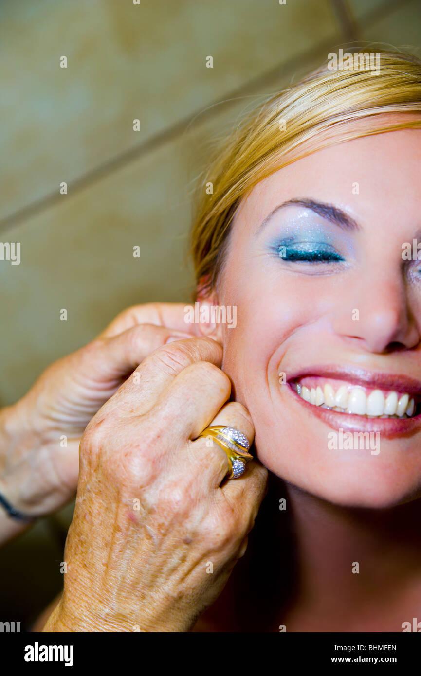 Fixing earring on a woman's ear Stock Photo