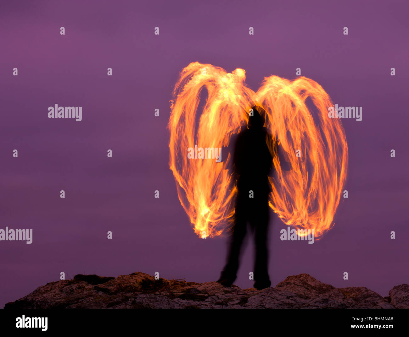 Man fire spinning (Fire Poi) on Cornish clifftops, Godrevy, Cornwall, England. Autumn (October) 2009 - Stock Image