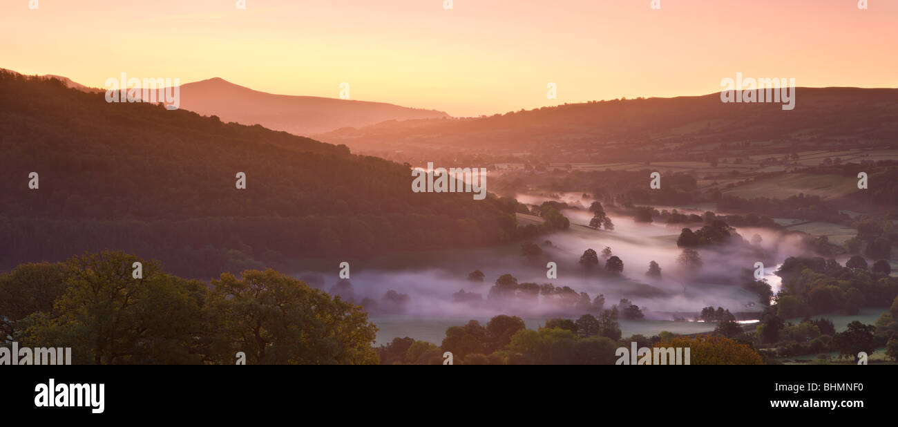 Mist lingers in the Usk Valley at dawn looking towards Sugar Loaf mountain, Brecon Beacons National Park, Powys, Stock Photo