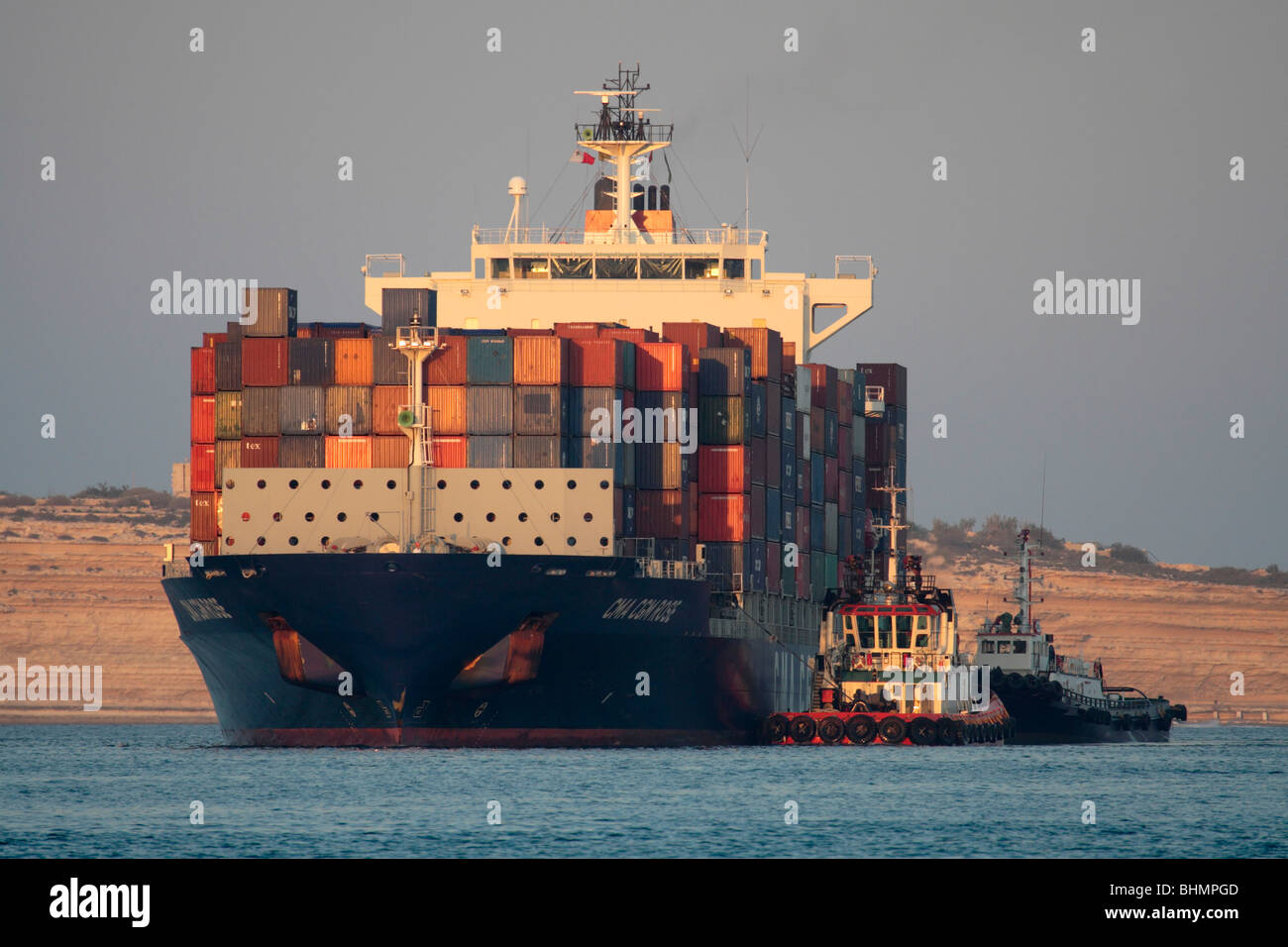 International trade by sea transport. Container ship accompanied by tugboats as it enters the Malta Freeport. Shipping - Stock Image
