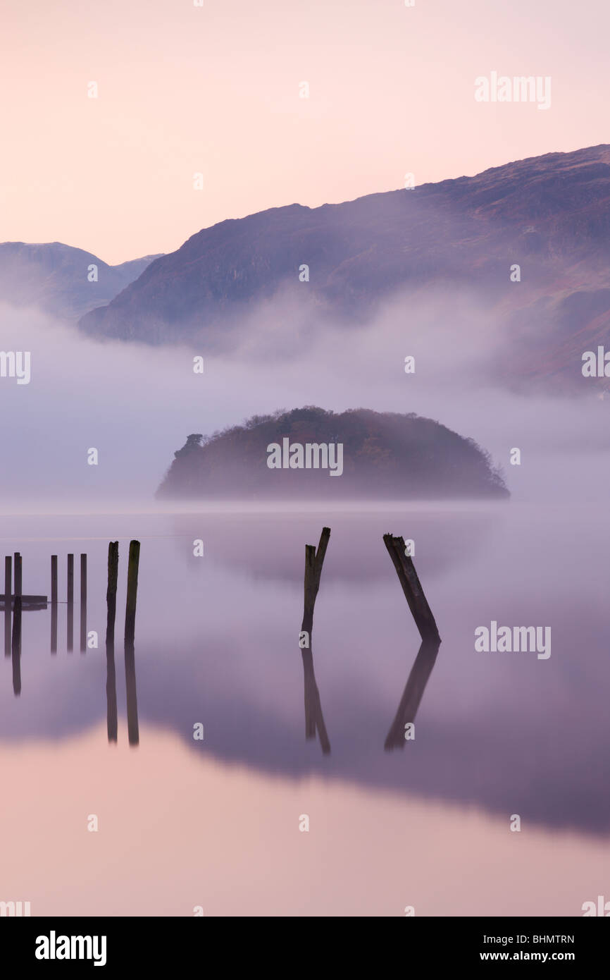 Wooden posts and St Herbert's Island on Derwent Water at dawn on a misty morning, Lake District National Park, - Stock Image
