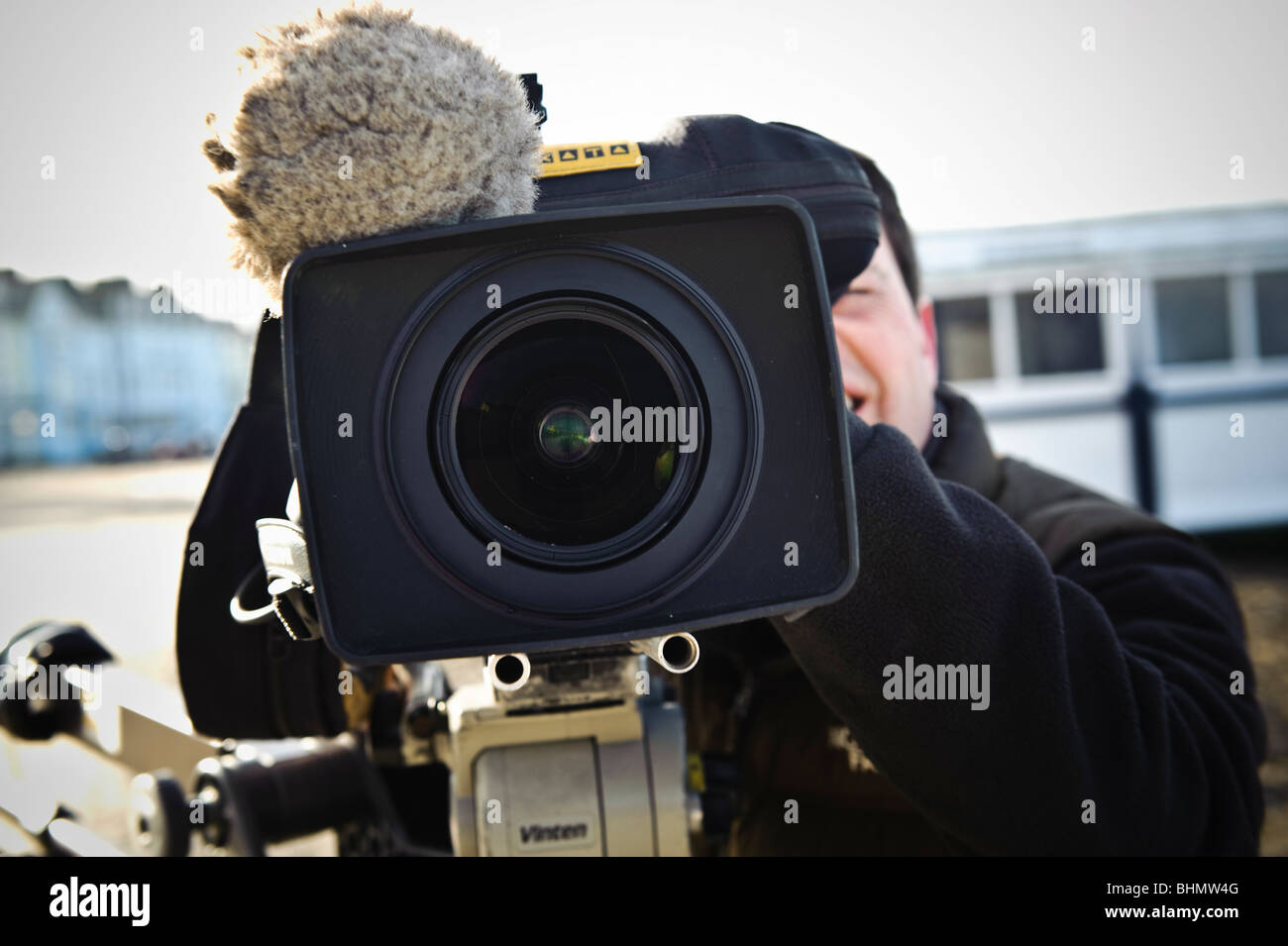 tv film crew recording news item - close up of video camera lens and cameraman - Stock Image