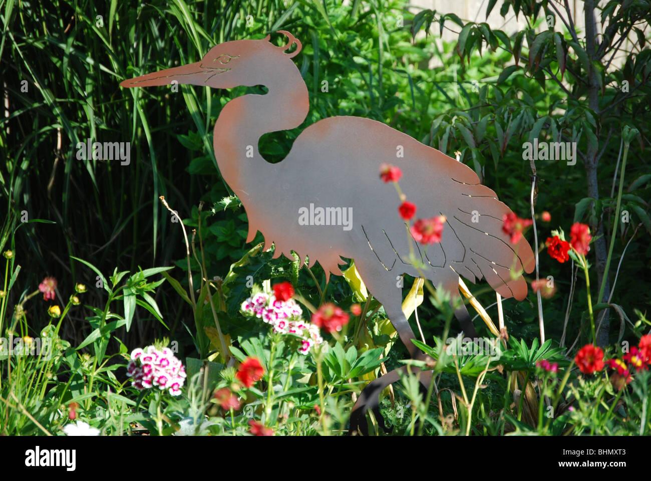 A Metal Garden Sculpture Of A Great Blue Heron In A Home Flower Garden.