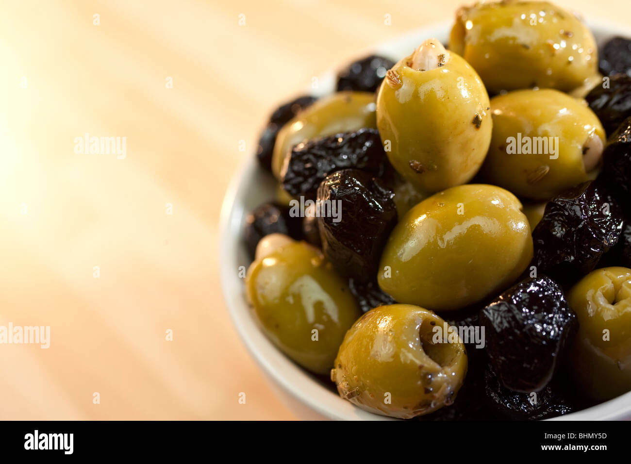 Close up macro photograph of a bowl of stuffed green and black Italian olives - Stock Image