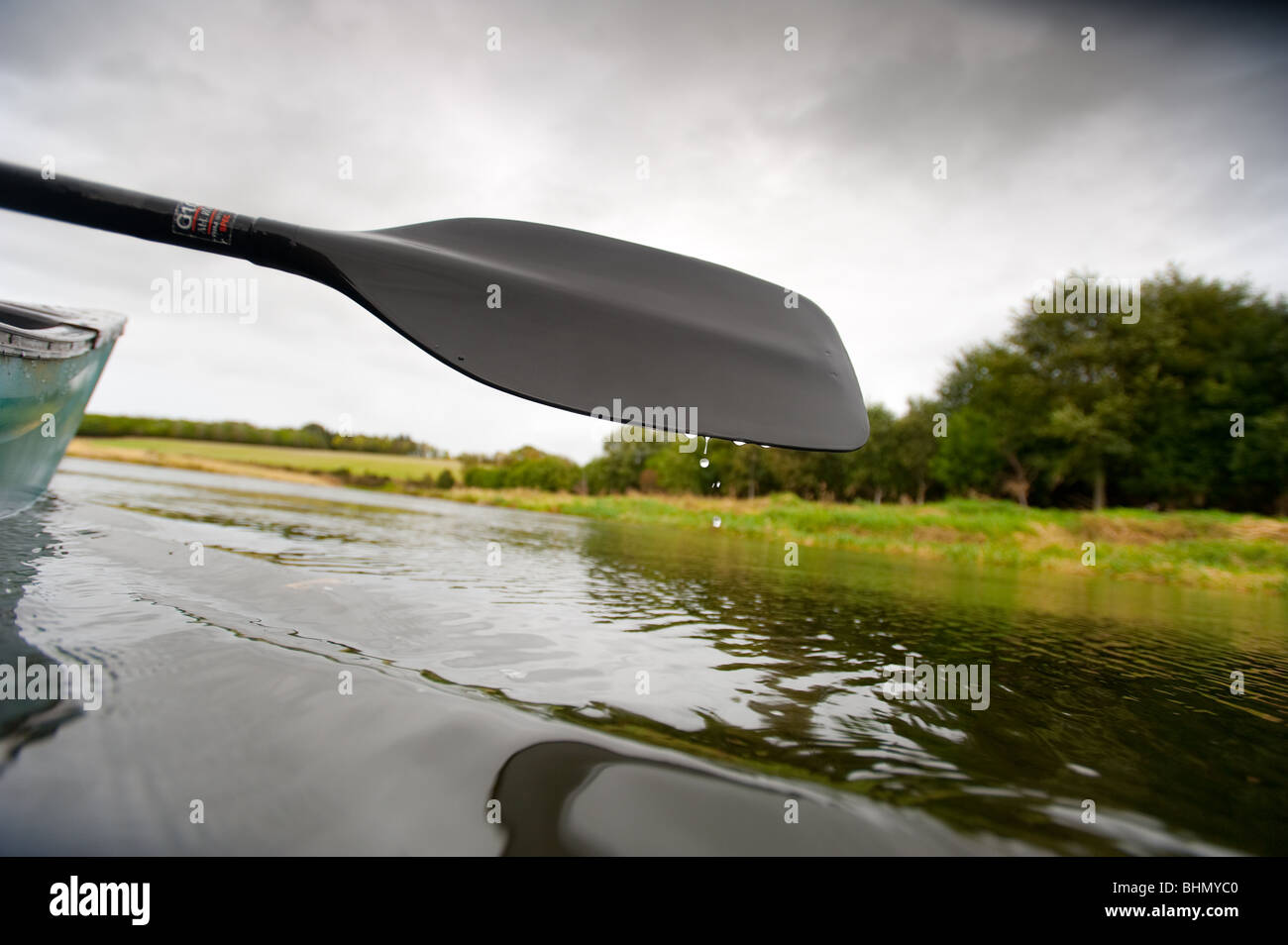 image of water droplets falling off canoe oar - Stock Image