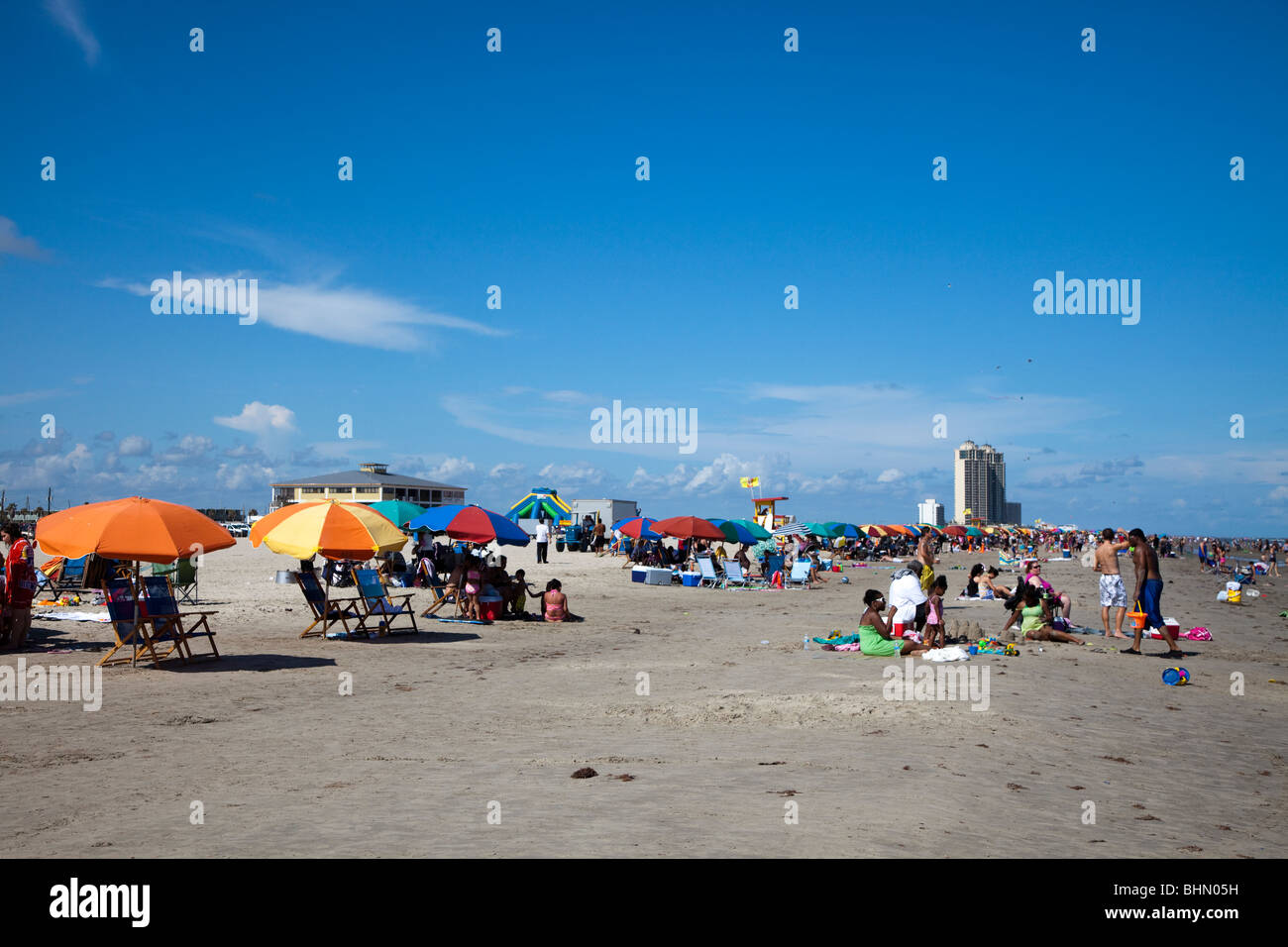 People on Stewart beach with sunshades and deckchairs Galveston Texas USA - Stock Image