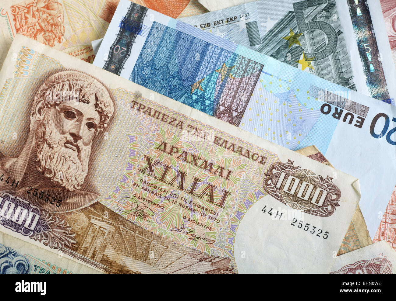 A mixture of old Greek drachma banknotes and euro notes that succeeded them. - Stock Image