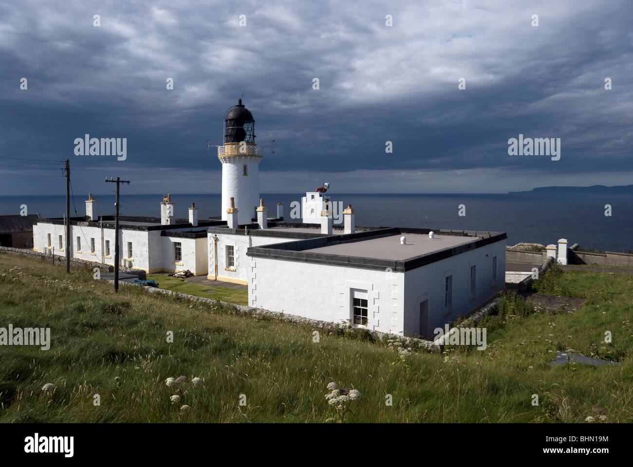The lighthouse at Dunnet Head on the north coast of Scotland with the Island of Stroma in the background. - Stock Image