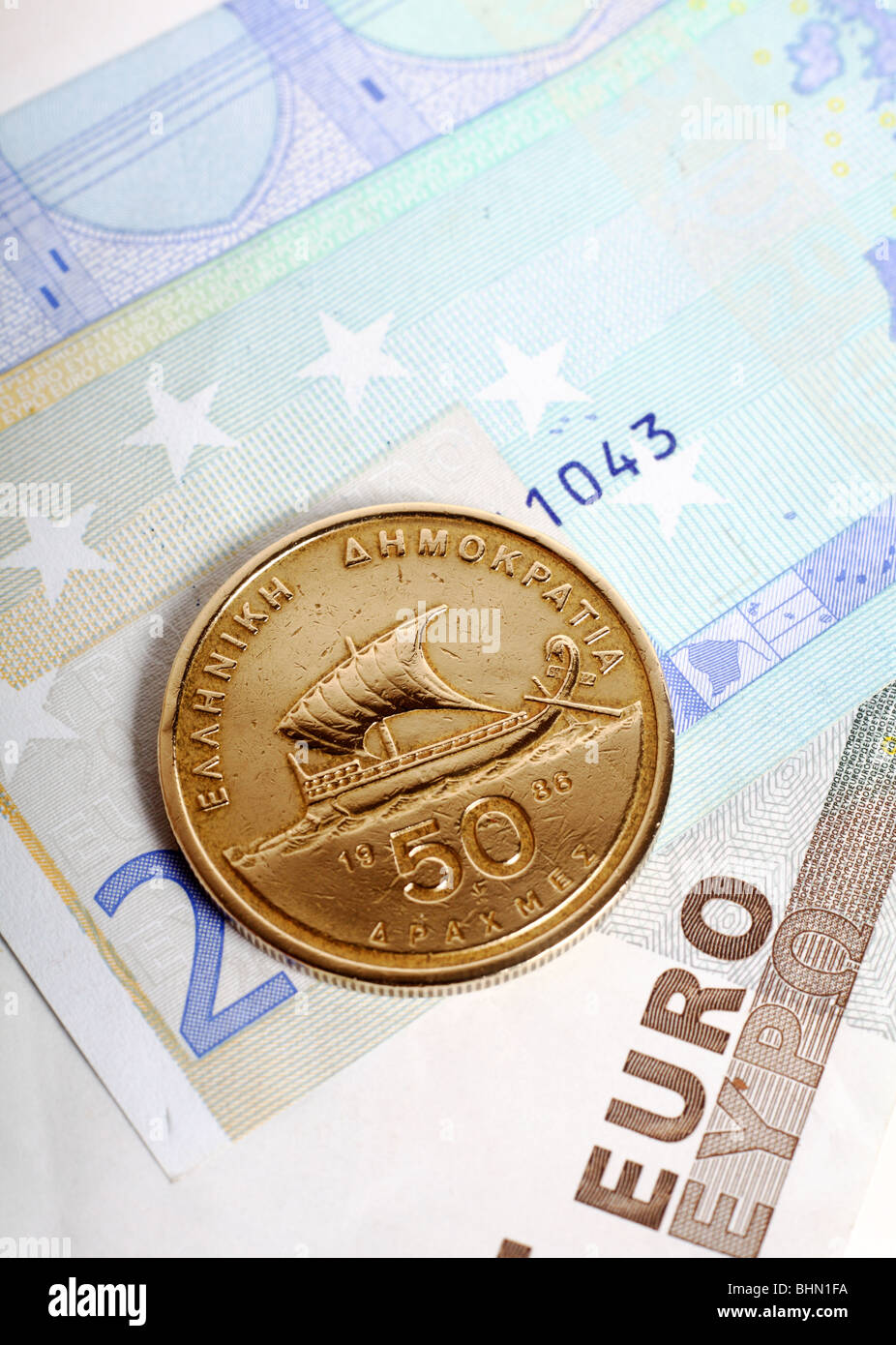 A fifty drachma coin on euro notes which replaced the currency. Greece's economic woes are  seen as a threat - Stock Image