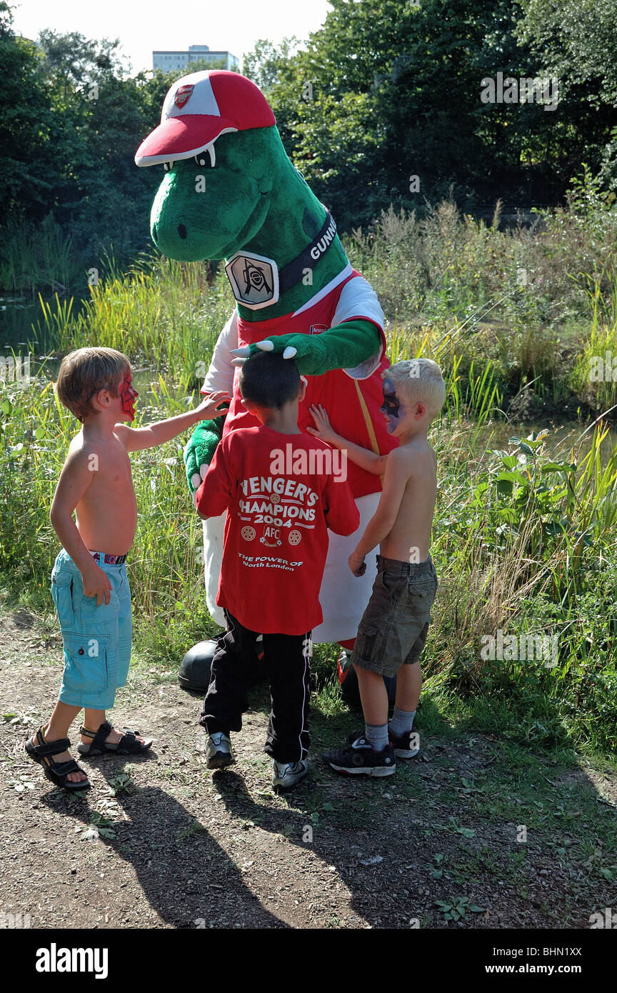 Gunnersaurus, Arsenal's mascot , talking to three small boy at the Gillespie Park Festival Highbury London England - Stock Image
