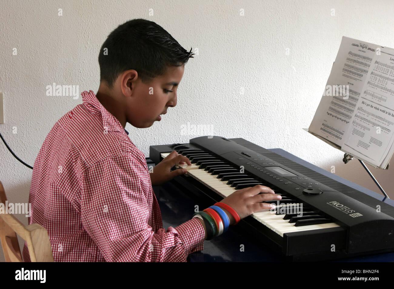 Teenage boy making music  at synthesizer keyboard - Stock Image