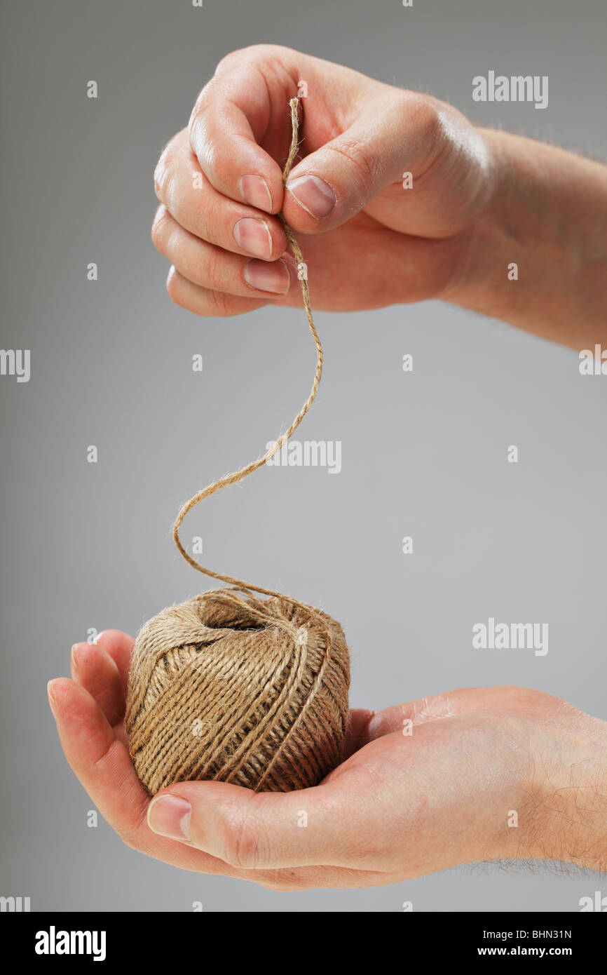 Hand holding a roll of natural fibre string - Stock Image