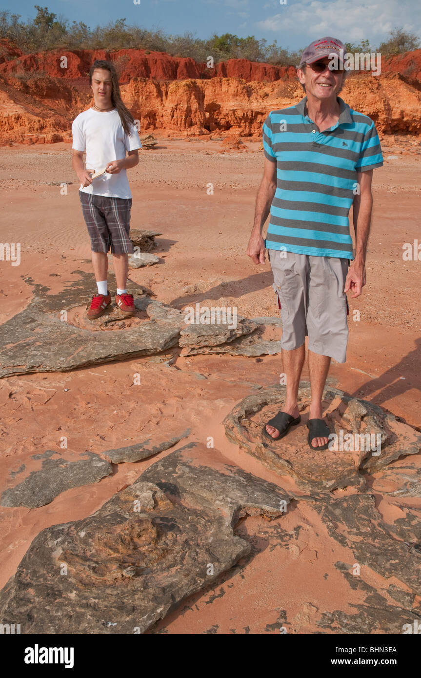 Two people standing in dinosaur footprints in fossilised mud on a beach near Broome - Stock Image