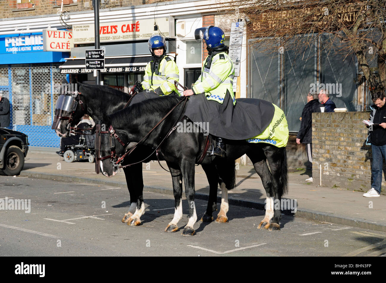 Police Horses with female riders policing an Arsenal match Highbury London England UK - Stock Image