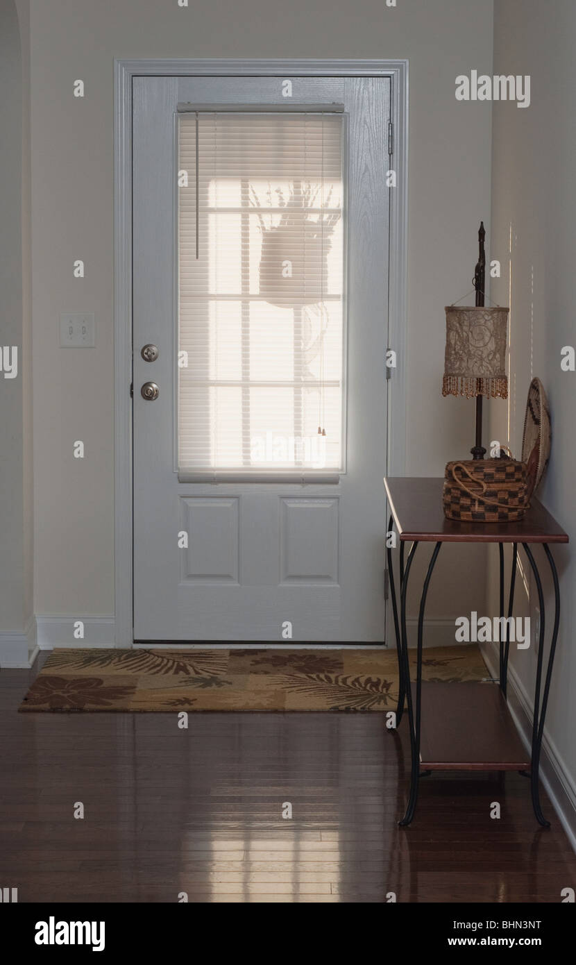 Entrance door of a family home, blinds on the door with shadow of flowers in a basket. Hardwood floor and entrance - Stock Image