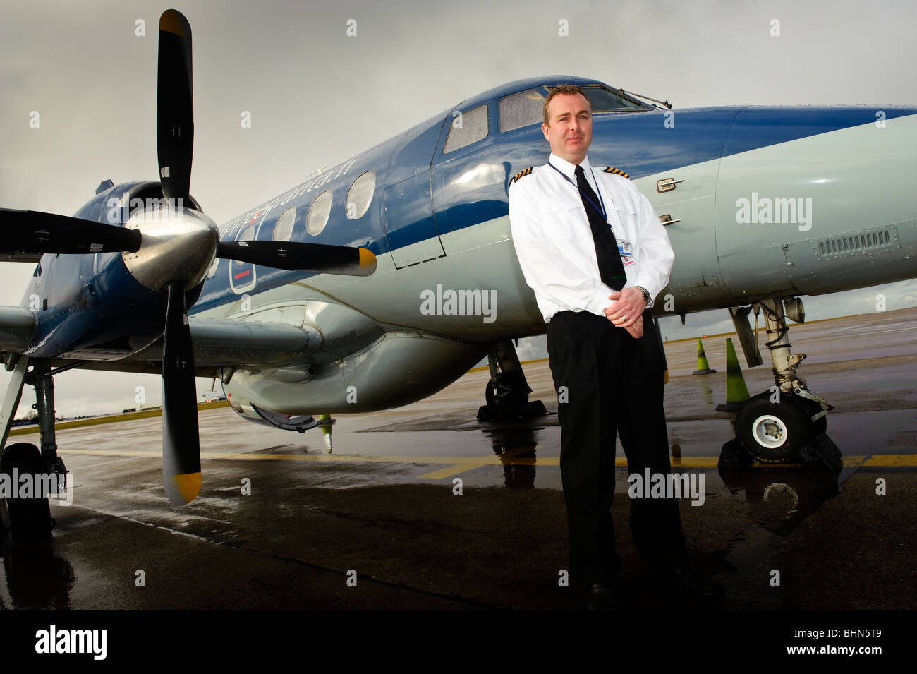 Elliston Miller,pilot with Highland Airways, with small turbo-prop commuter airplane at Cardiff Airport, south Wales - Stock Image