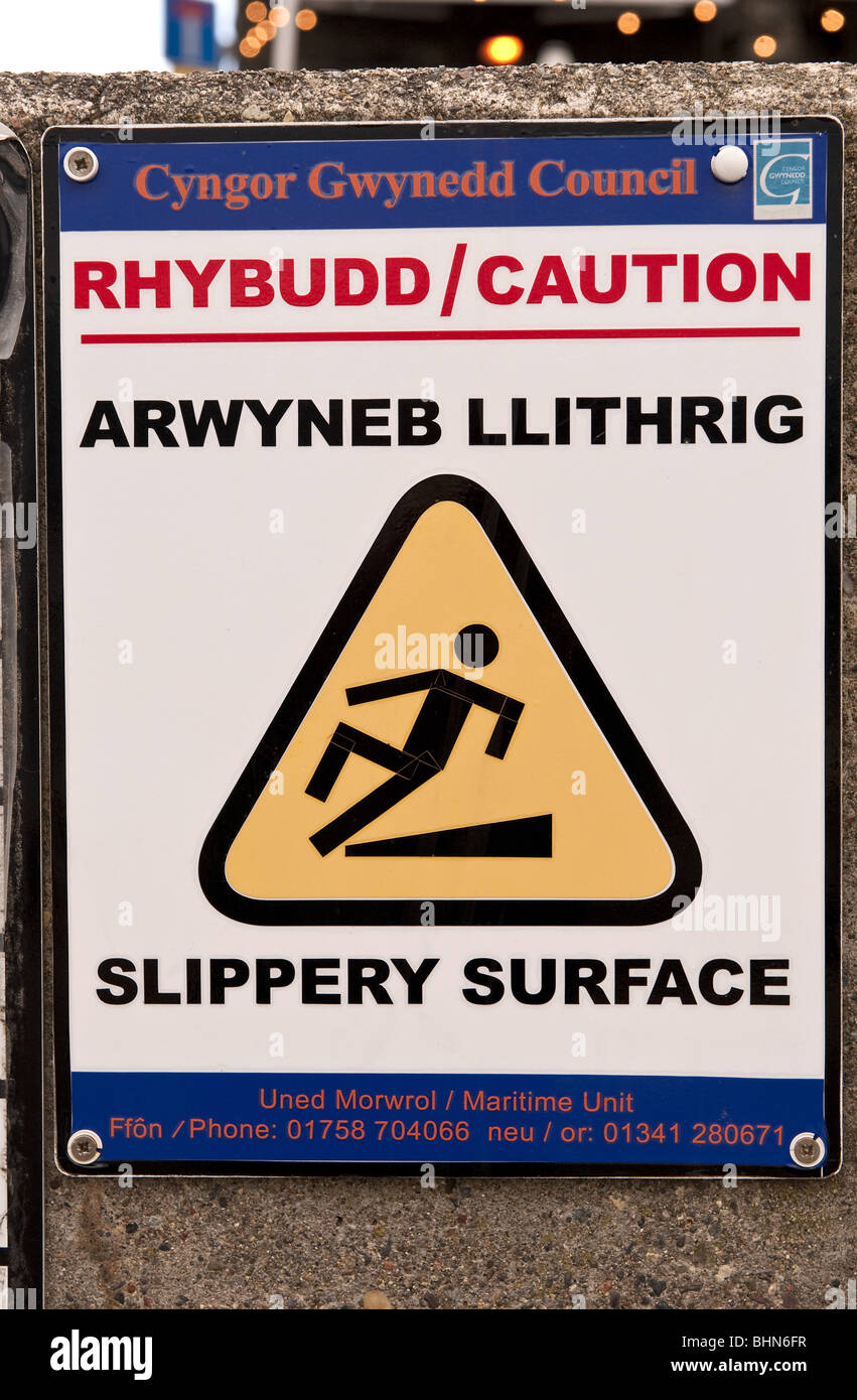 Bilingual Gwynedd Council sign warning of slippery surface in English and Welsh - Stock Image