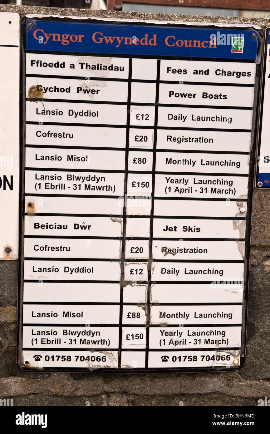 Bi-lingual harbour sign illustrating the fees and charges for boating and sailing related activities posted by Gwynedd - Stock Image