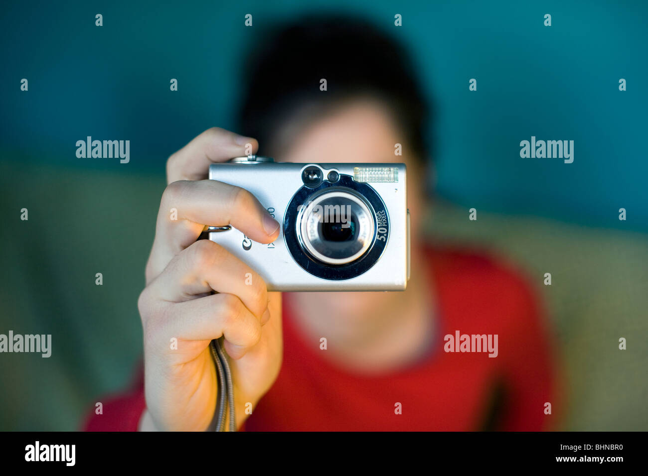 Young woman takes photo with digital camera, London - Model Released - Stock Image