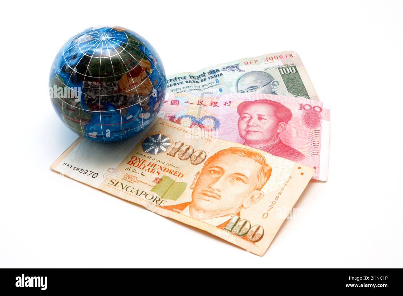 Asian currencies with miniature globe. Singapore 100 dollar bill, Chinese 100 yuan and Indian 100 rupees. - Stock Image