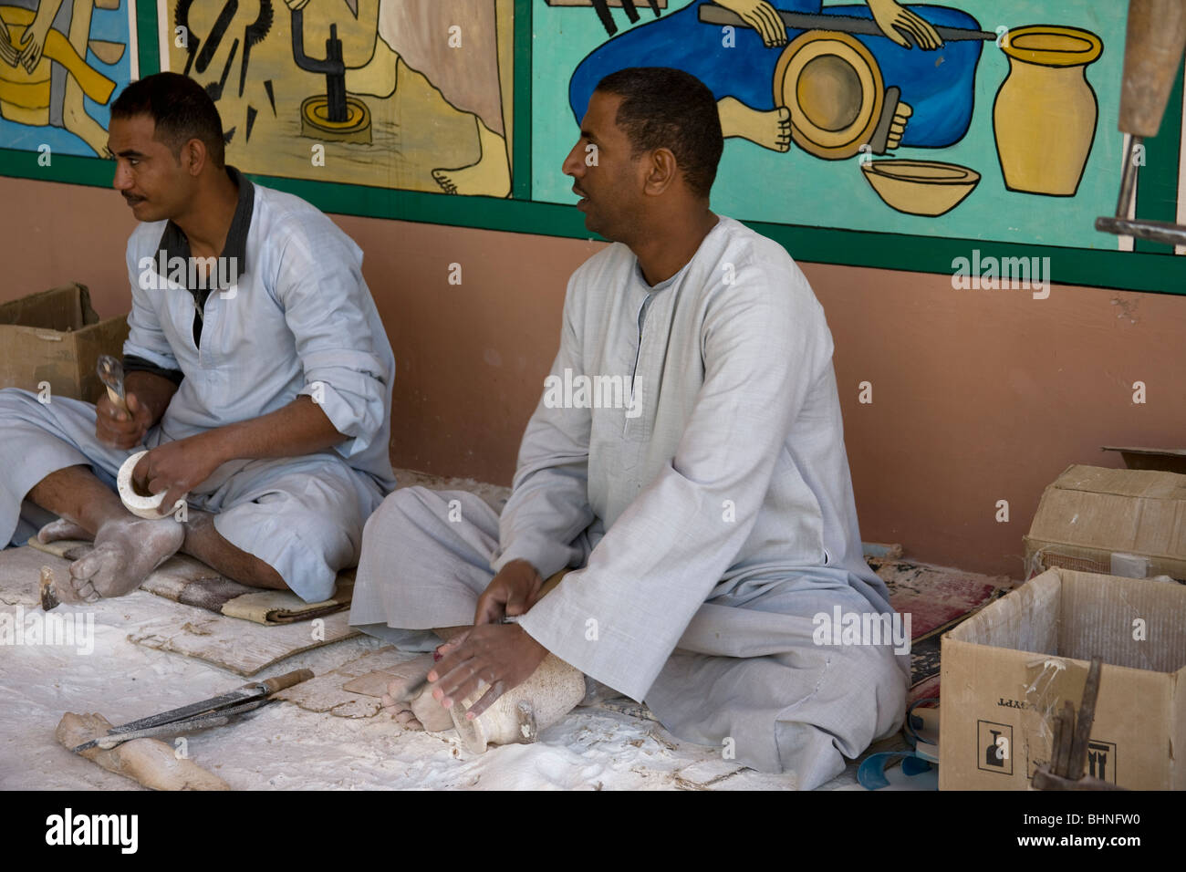 Craftsmen working, refining  alabaster vases outside a shop. - Stock Image