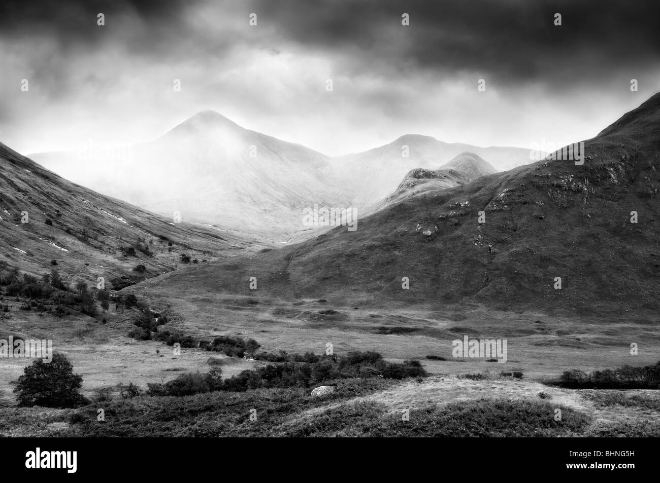 Black and white picture of Glen Etive, Glencoe region in Scotland with mist and rain coming in, taken in early autumn - Stock Image
