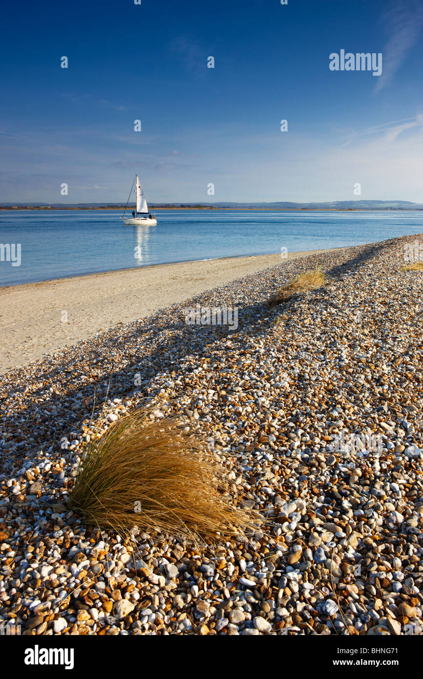 A lone sailing boat sails out to sea, East Head, West Wittering - Stock Image