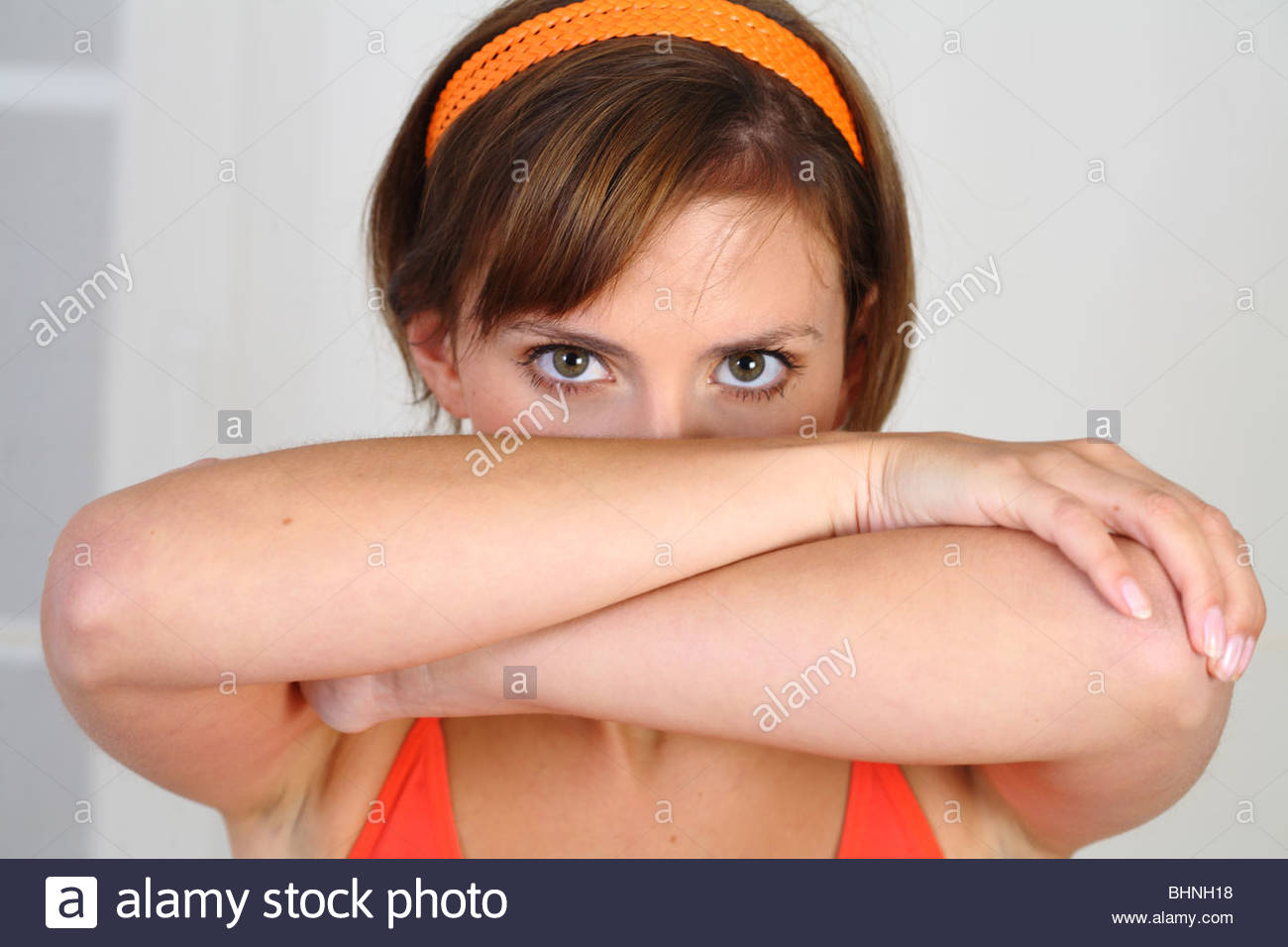 portrait brunette woman covering her face with arms Stock Photo